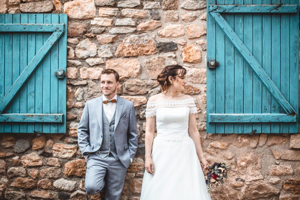 Couple posant devant mur et volet de couleurs bleu