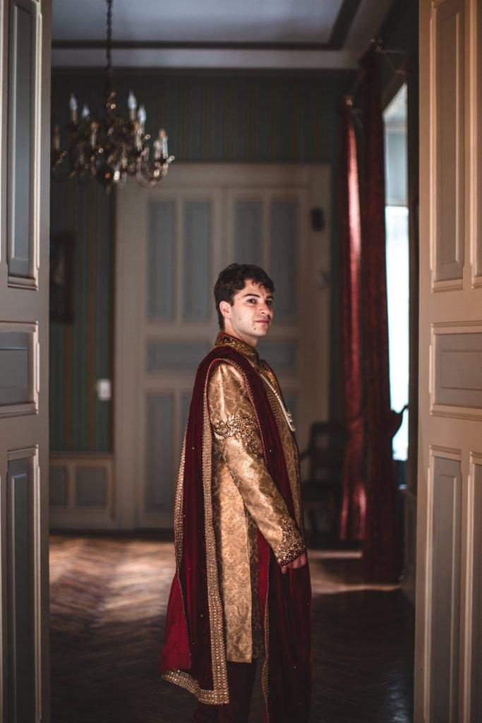 MArié en tenue de cérémonie indienne dans l'encadrement d'une porte du château