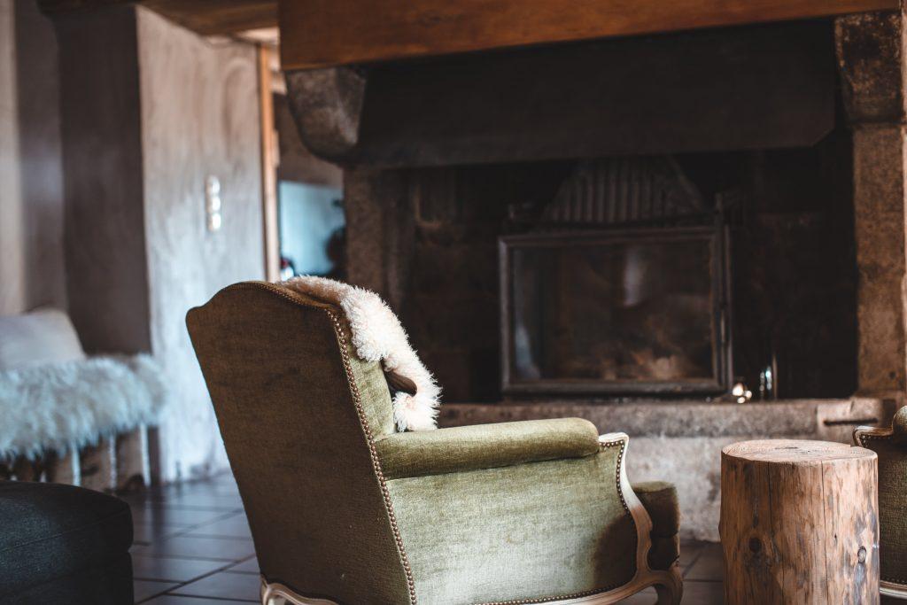 Fauteuil au coin du feu dans une ambiance de gite rustique