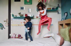 Photographe-Famille-Enfants jouant en sautant sur leur lit