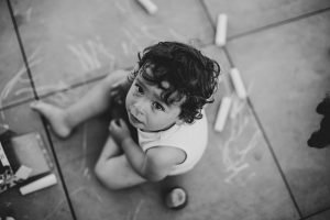 Photographe-Famille-Clermont-Ferrand-Enfant assis au sol dessinant avec des craies