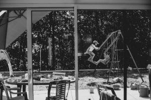 Photographe-Famille-Clermont-Ferrand-Deux enfants jouent sur une balançoire dans le jardin